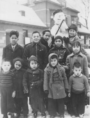 HVB FO 00553  Indonesische kinderen met sneeuwpop voor station Bergen, 30 maart 1952. Ze woonden in het Oranjehotel